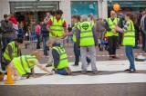 Project Manager Fiona Sturley and volunteers lay the performance matting in the Market Place