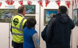 Volunteer Mike French and others take time out to enjoy the Mark Bromley paintings
